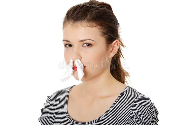 Mujer adolescente con el tejido en su nariz imagen de archivo