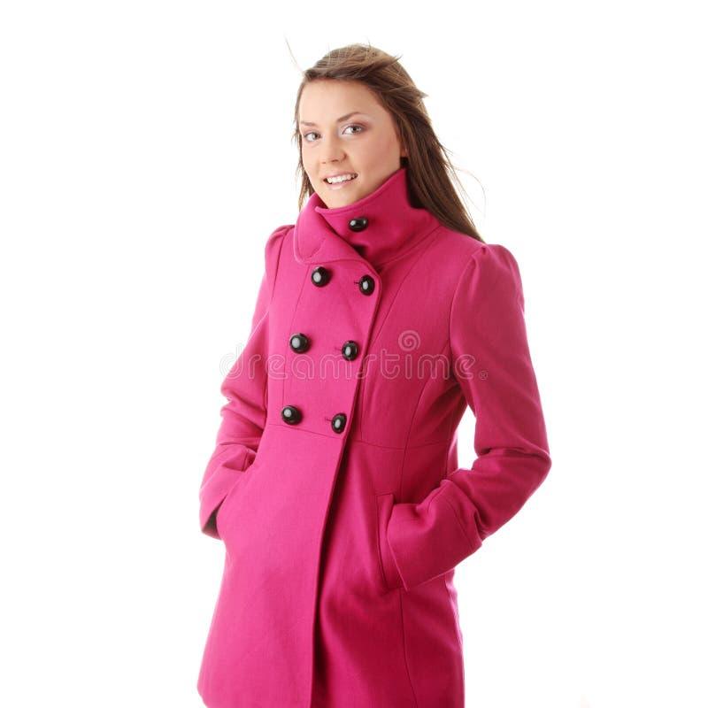 Mujer adolescente en capa femenina rosada imagenes de archivo