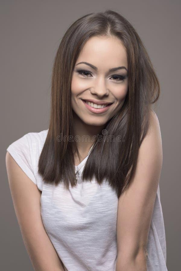 Mujer adolescente joven sonriente magnífica que mira la cámara con el pelo marrón recto imagenes de archivo