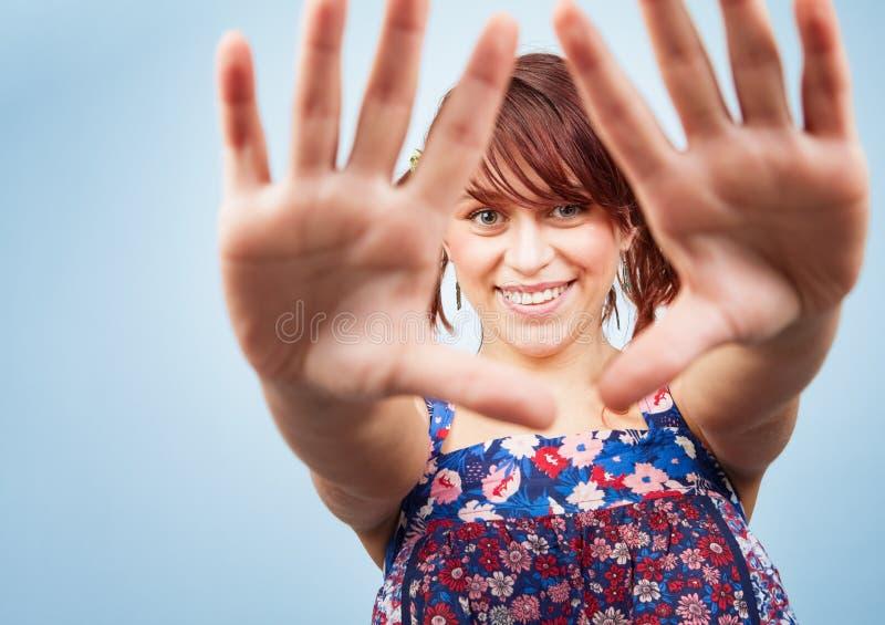 Mujer adolescente juguetona feliz que mira a través de las manos fotos de archivo libres de regalías
