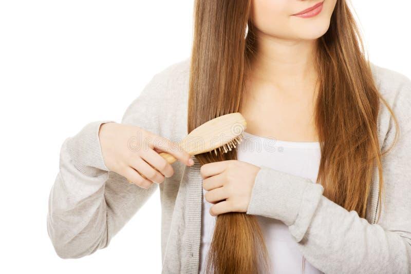 Mujer adolescente que cepilla su pelo fotografía de archivo
