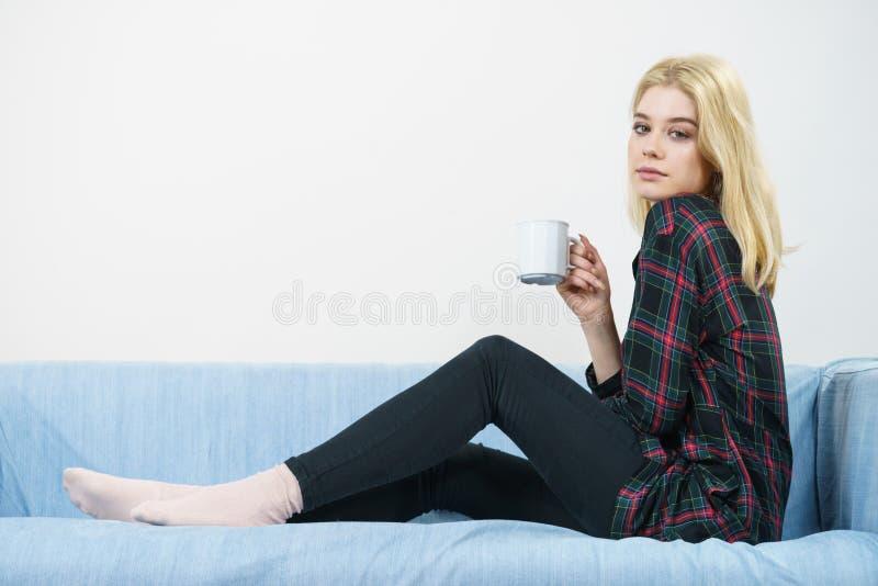 Mujer adolescente que se sienta en el sof? con la taza fotos de archivo