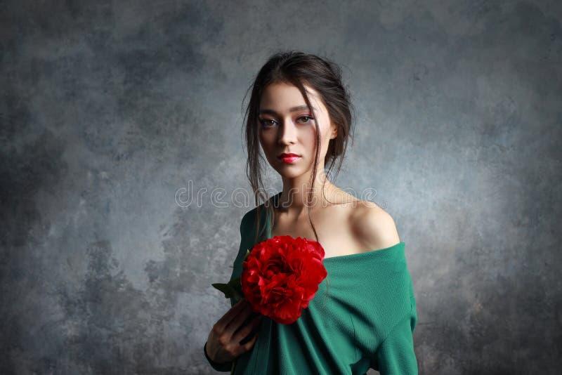 Mujer adorable que lleva el vestido elegante que sostiene una flor roja de la peonía fotografía de archivo libre de regalías