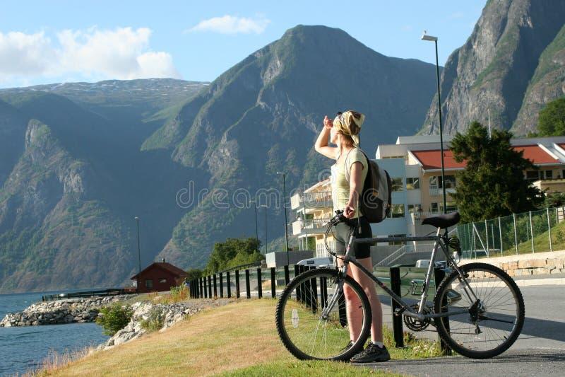 Mujer adulta con la bici que mira las montañas foto de archivo libre de regalías