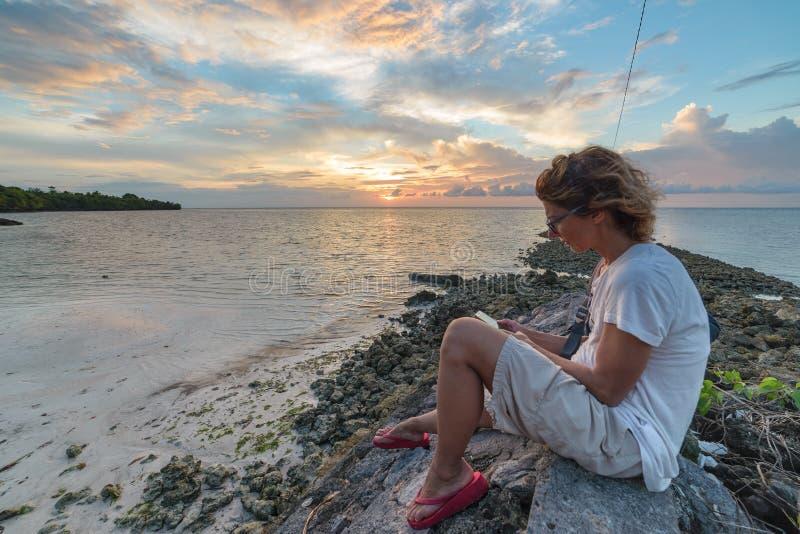 Mujer adulta con las lentes que lee el ebook que se relaja en el concepto dramático de las vacaciones de los días de fiesta del c fotos de archivo