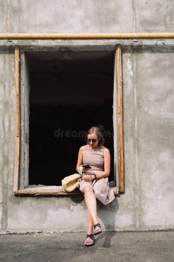 Mujer adulta en vestido usando móvil en travesaño de la ventana imágenes de archivo libres de regalías