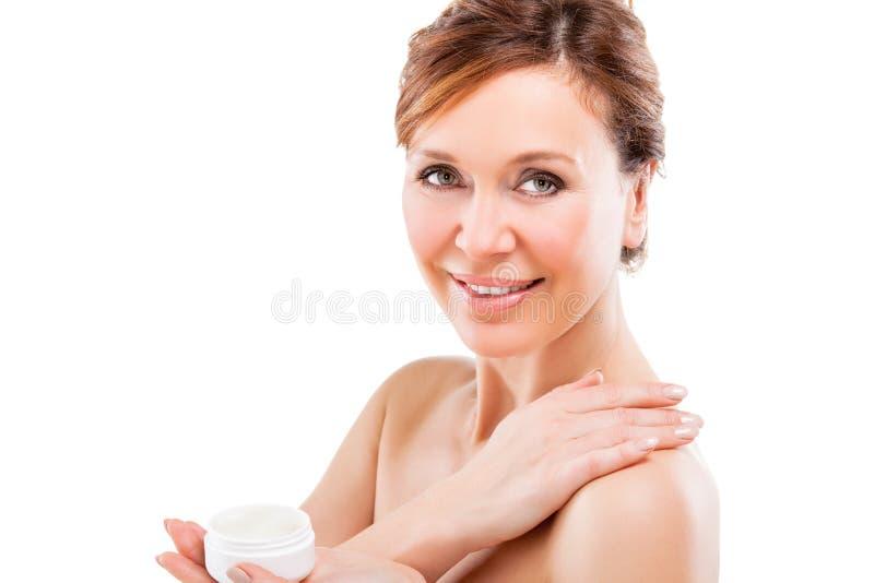 Mujer adulta hermosa que aplica la crema. fotografía de archivo libre de regalías