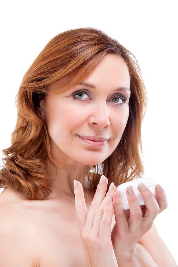 Mujer adulta hermosa que aplica la crema en cara. fotos de archivo