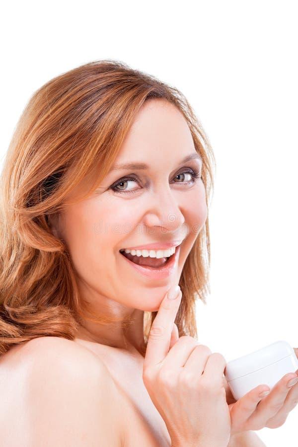 Mujer adulta hermosa que aplica la crema en cara. fotos de archivo libres de regalías