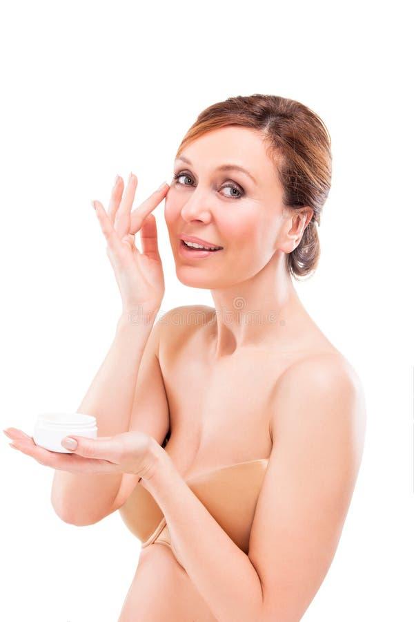 Mujer adulta hermosa que aplica la crema en cara. fotografía de archivo