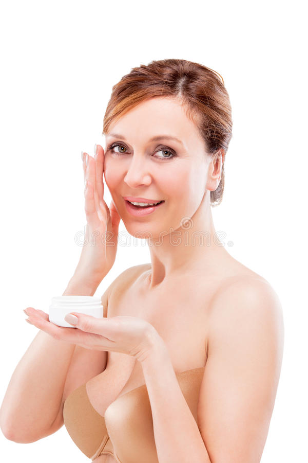 Mujer adulta hermosa que aplica la crema en cara. imagenes de archivo