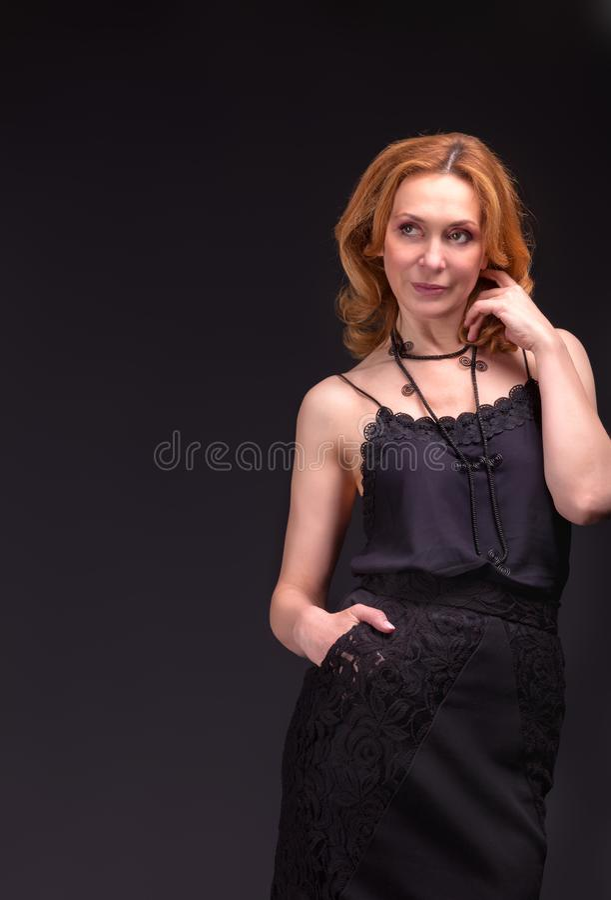 Mujer adulta hermosa que presenta en el fondo negro foto de archivo libre de regalías