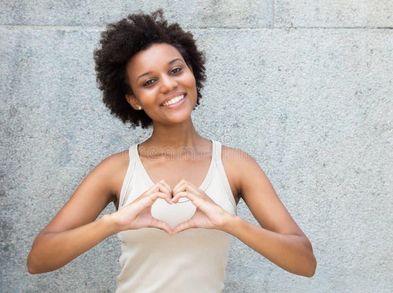 Mujer adulta joven afroamericana en el amor que muestra el corazón con la ha fotos de archivo