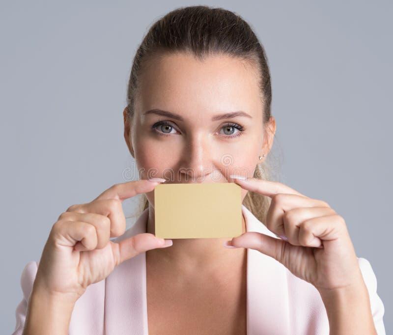 Mujer adulta joven con la tarjeta de crédito sobre el fondo blanco fotografía de archivo