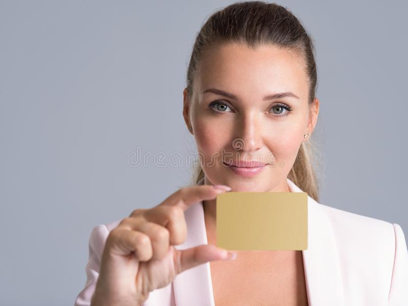 Mujer adulta joven con la tarjeta de crédito sobre el fondo blanco fotos de archivo