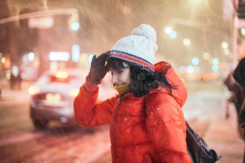Mujer adulta joven en la calle de la ciudad debajo de la tormenta de la nieve del invierno en la noche imagenes de archivo
