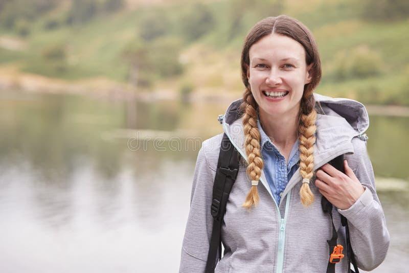 Mujer adulta joven en una acampada que hace una pausa un lago que ríe, retrato, distrito del lago, Reino Unido imagenes de archivo