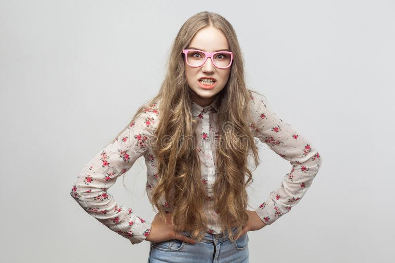 Mujer adulta joven enojada en lentes rosadas, y la camisa, mirando a fotos de archivo libres de regalías