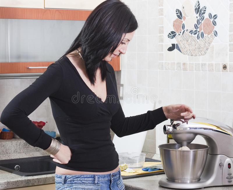 Mujer adulta joven que cocina en el país imagenes de archivo