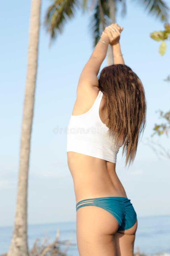 Mujer adulta joven que estira en la playa imágenes de archivo libres de regalías