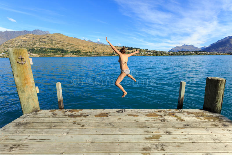 Mujer adulta joven que salta adentro al lago con alegre imagen de archivo