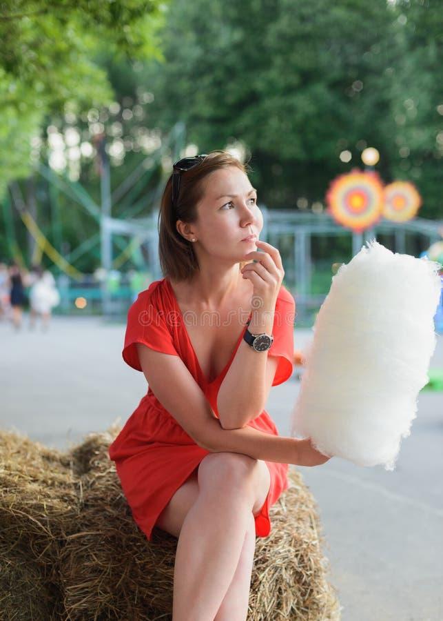 Mujer adulta joven que se sienta en la bala de heno y que celebra el caramelo de algodón blanco en el parque de atracciones imagen de archivo