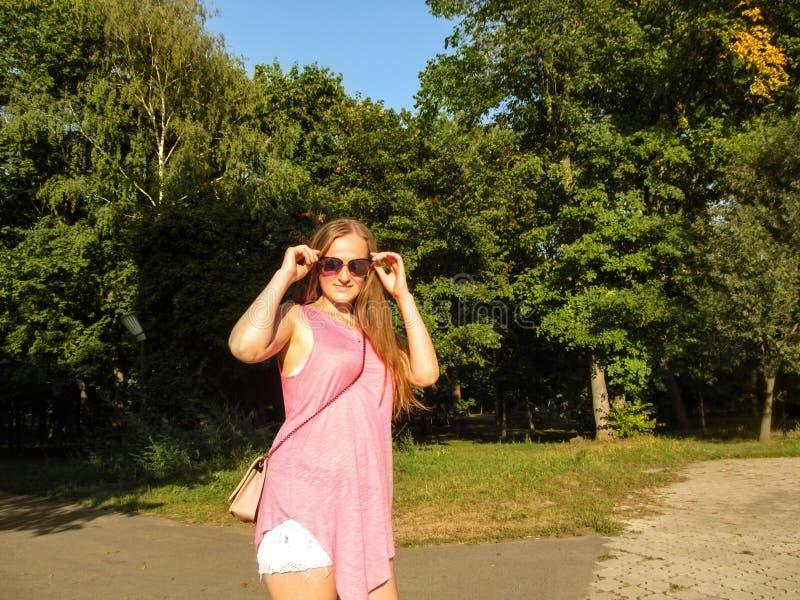 Mujer adulta joven, sonriendo, para sacar alrededor las gafas de sol mientras que se coloca en parque muchacha Rubio-cabelluda co fotografía de archivo