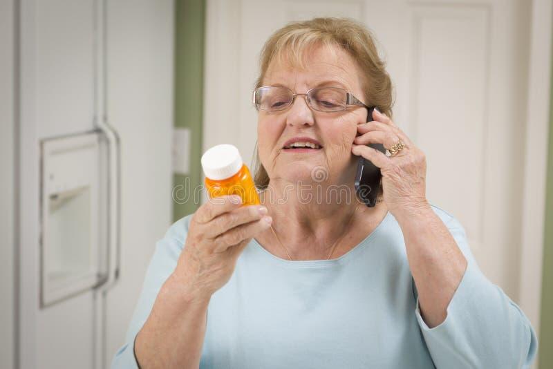 Mujer adulta mayor en el teléfono celular que sostiene la botella de la prescripción fotografía de archivo libre de regalías