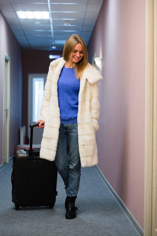 Mujer adulta positiva que se coloca en pasillo con equipaje lleno imagen de archivo