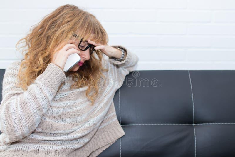 Mujer adulta preocupante que habla en móvil fotografía de archivo libre de regalías