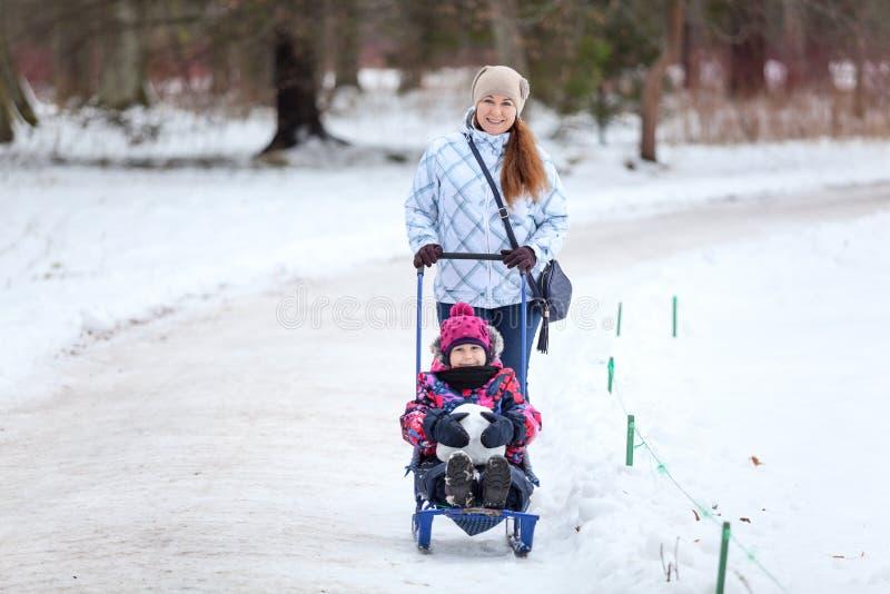 Mujer adulta que camina con su bebé en el parque del invierno, tirando del trineo con la hija en camino de la nieve, copyspace imagen de archivo libre de regalías