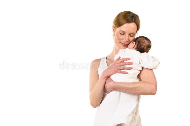 Mujer adulta que detiene al bebé en sus brazos foto de archivo libre de regalías