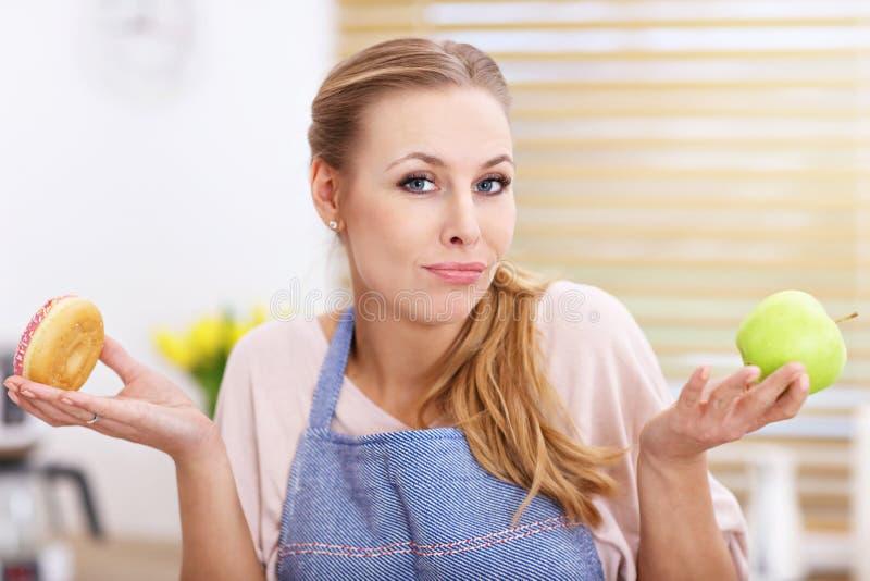 Mujer adulta que elige entre la manzana y el buñuelo en la cocina fotos de archivo libres de regalías