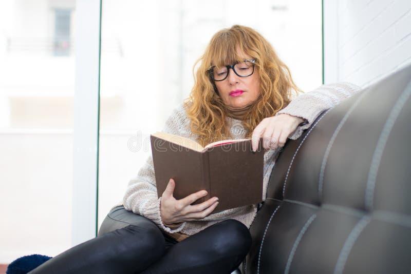 Mujer adulta que lee el libro imagen de archivo