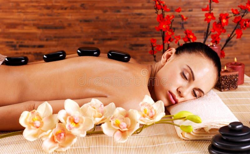 Mujer adulta que se relaja en salón del balneario con las piedras calientes encendido detrás foto de archivo libre de regalías
