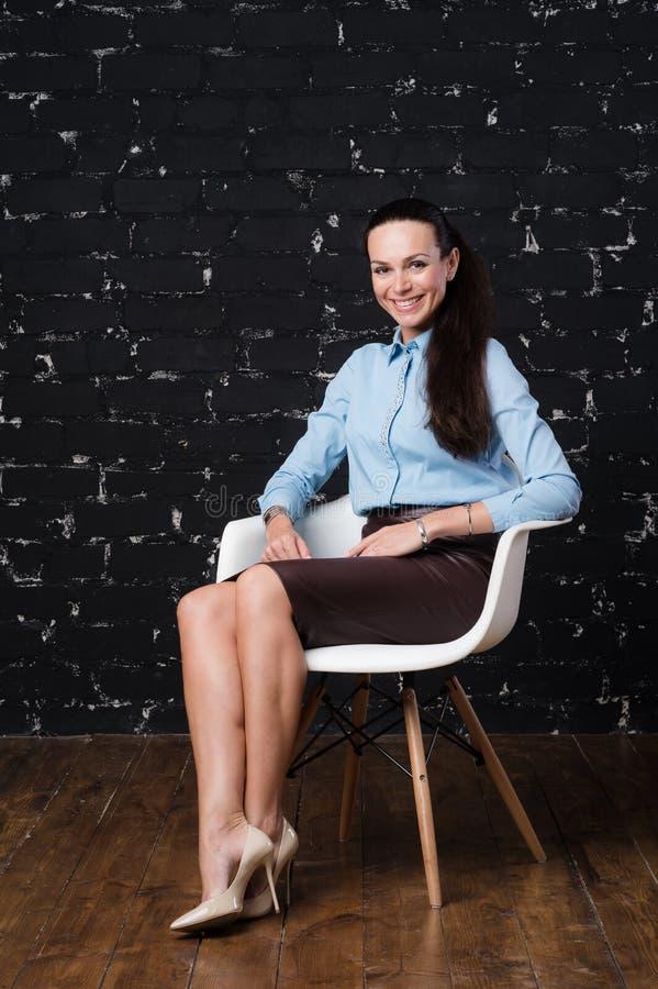 Mujer adulta que se sienta en una silla en ladrillo negro del fondo fotografía de archivo