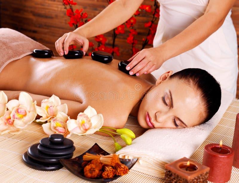 Mujer adulta que tiene masaje de piedra caliente en salón del balneario fotos de archivo libres de regalías