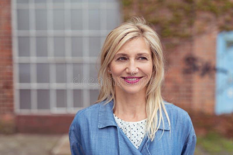 Mujer adulta rubia sonriente fuera del edificio fotografía de archivo libre de regalías