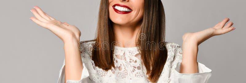 Mujer adulta sonriente con el pelo marrón largo que sostiene hacia fuera su palma que mira una mano imágenes de archivo libres de regalías