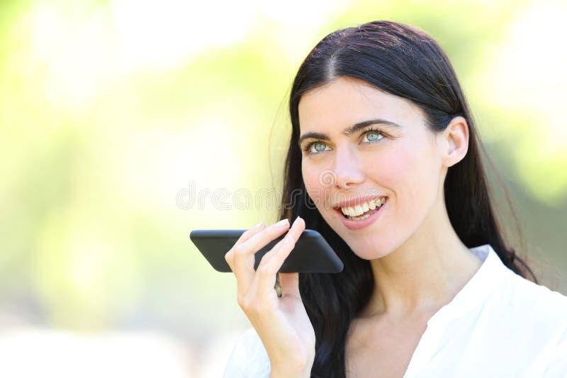 Mujer adulta usando el reconocimiento vocal en el teléfono fotografía de archivo libre de regalías