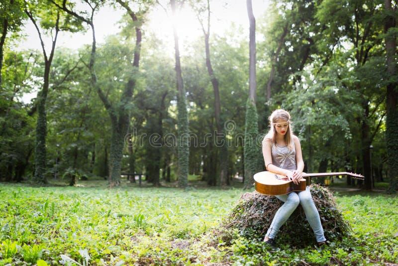 Mujer afligida en naturaleza con la guitarra fotos de archivo libres de regalías