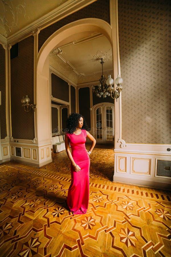 Mujer africana atractiva hermosa en el vestido rojo que presenta en los apartamentos de lujo imagen de archivo