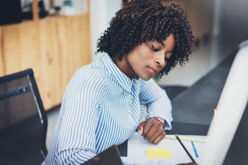 Mujer africana atractiva joven que trabaja con los papeles en oficina moderna La oscuridad peló a la muchacha que hacía notas en  imagenes de archivo