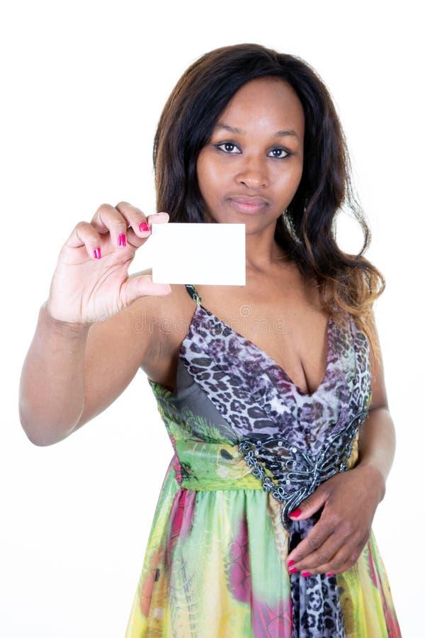 Mujer africana atractiva que sostiene su tarjeta de visita vac?a en blanco blanca imagen de archivo