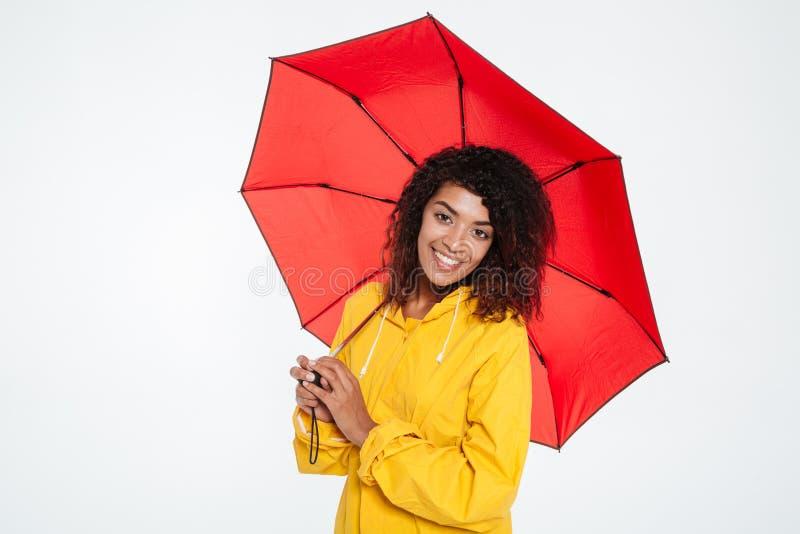 Mujer africana bastante feliz en el impermeable que presenta con el paraguas fotografía de archivo libre de regalías