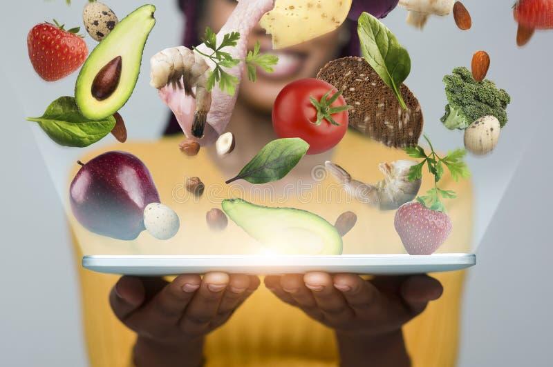 Mujer africana con el ordenador portátil que propone comprar verduras frescas fotos de archivo libres de regalías