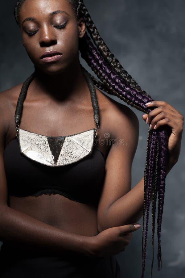 Mujer africana con el pelo muy largo trenzado en trenza multicolora foto de archivo libre de regalías