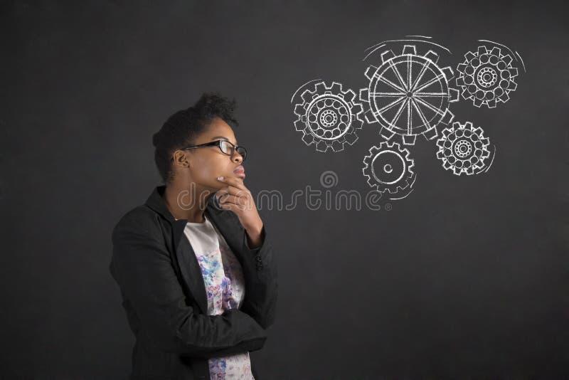 Mujer africana con la mano en la barbilla que piensa con los engranajes en fondo de la pizarra foto de archivo