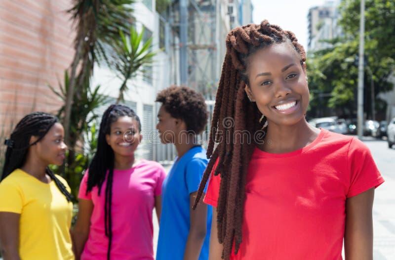 Mujer africana con los dreadlocks y novias en la ciudad imagen de archivo libre de regalías