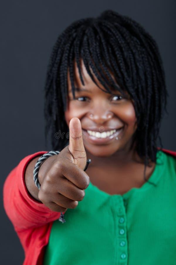 Mujer africana con los pulgares para arriba foto de archivo